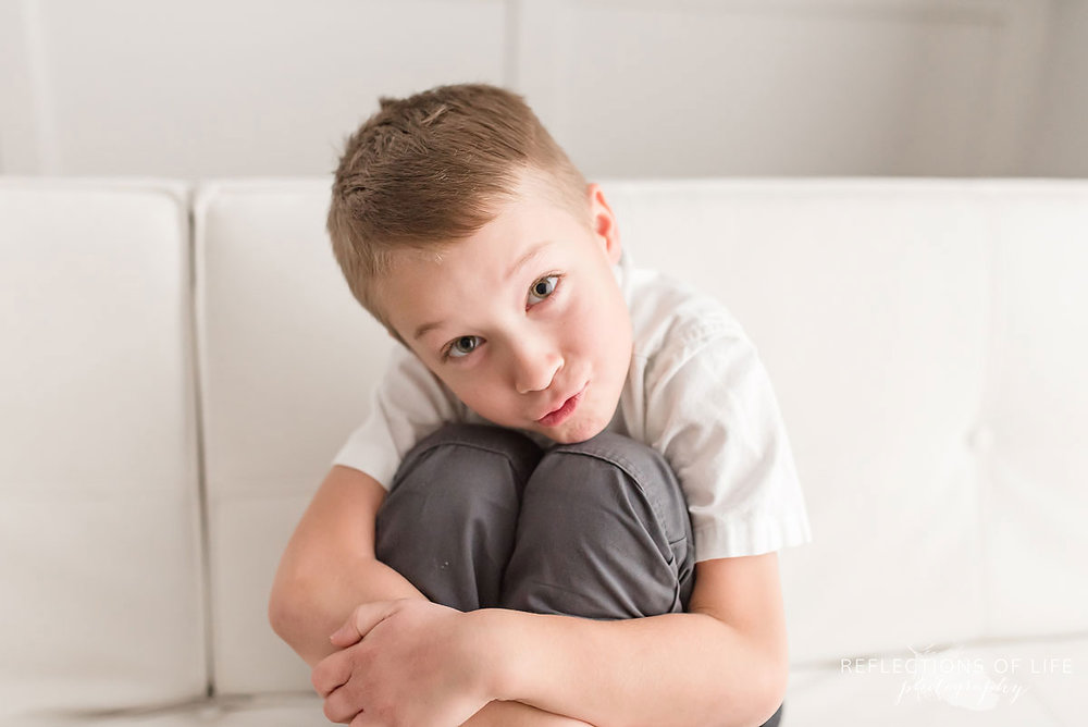 young boy sitting down hugging his knees.jpg