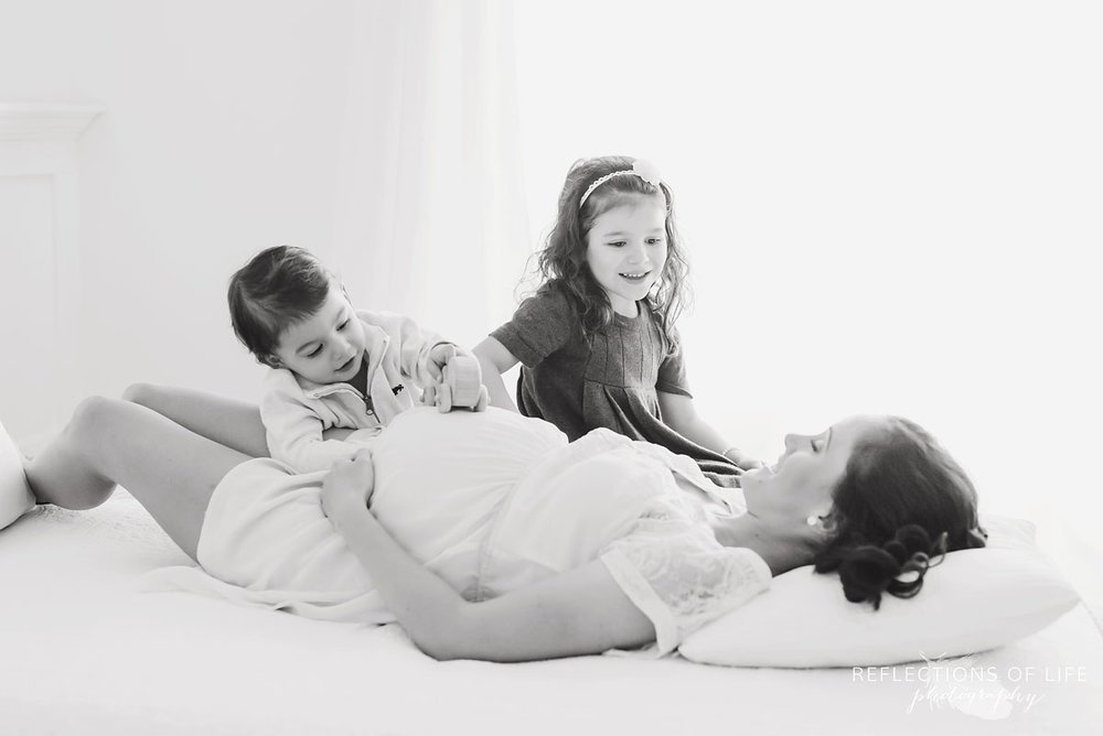 fun photography with siblings and pregnant mom