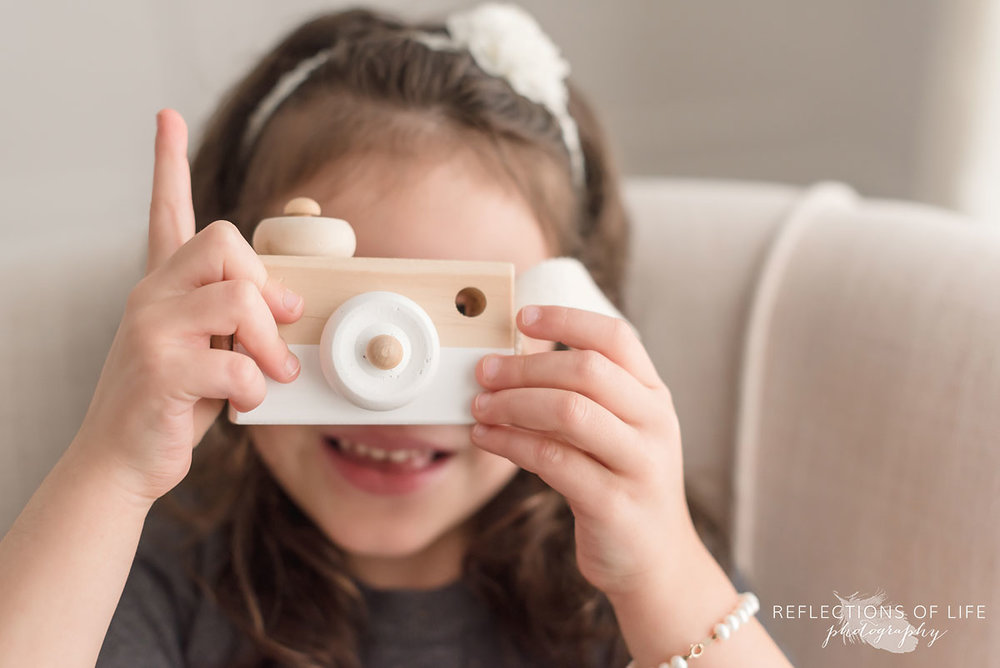 Cure child photos of young girl playing with wooden camera