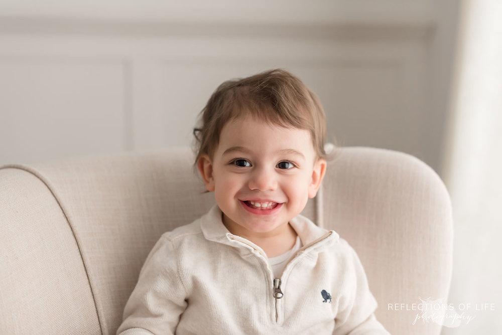 Young boy smiling at his dad natural light photo studio