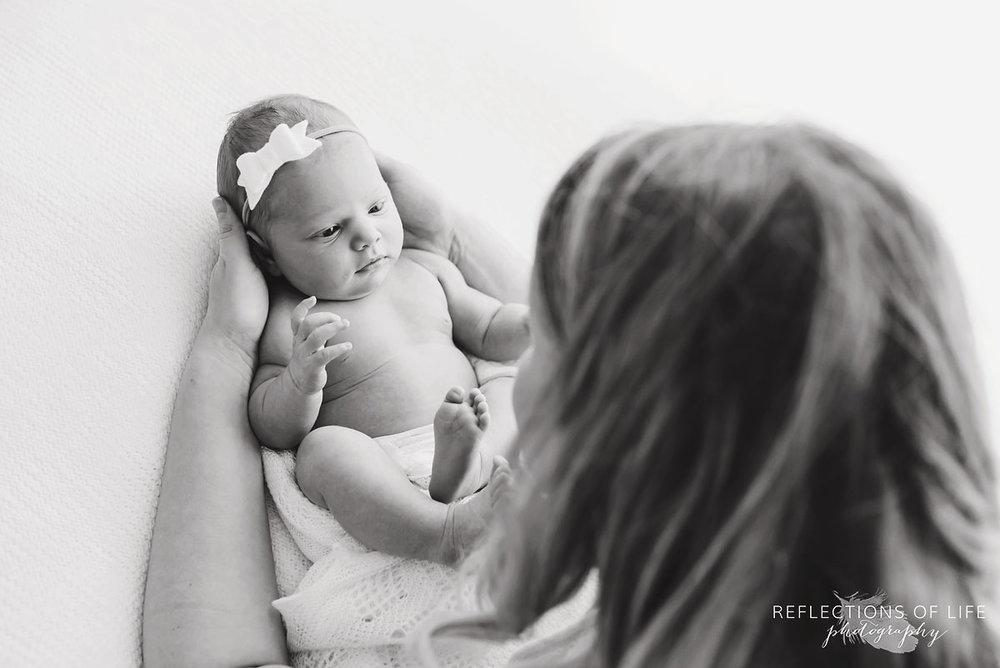 mother holding newborn baby girl wearing headband black and white