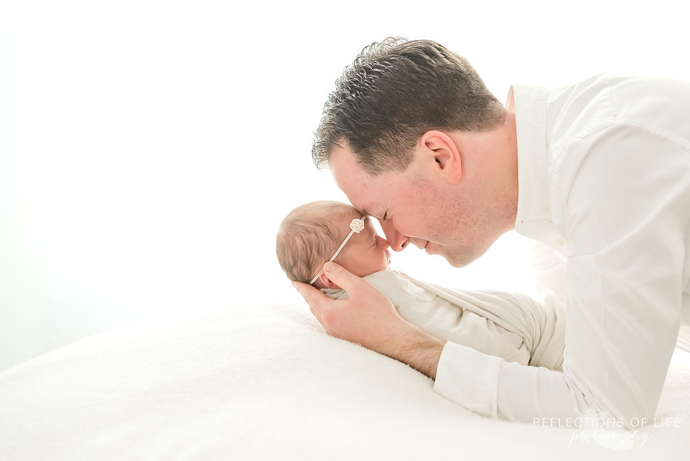 daddy and newborn baby girl rest heads together on beanbag in niagara region photo studio
