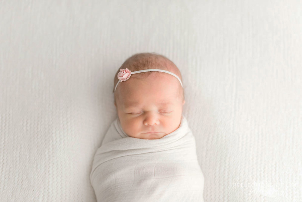 Little newborn bby girl swaddled in little white unicorn blanket with small rose headband