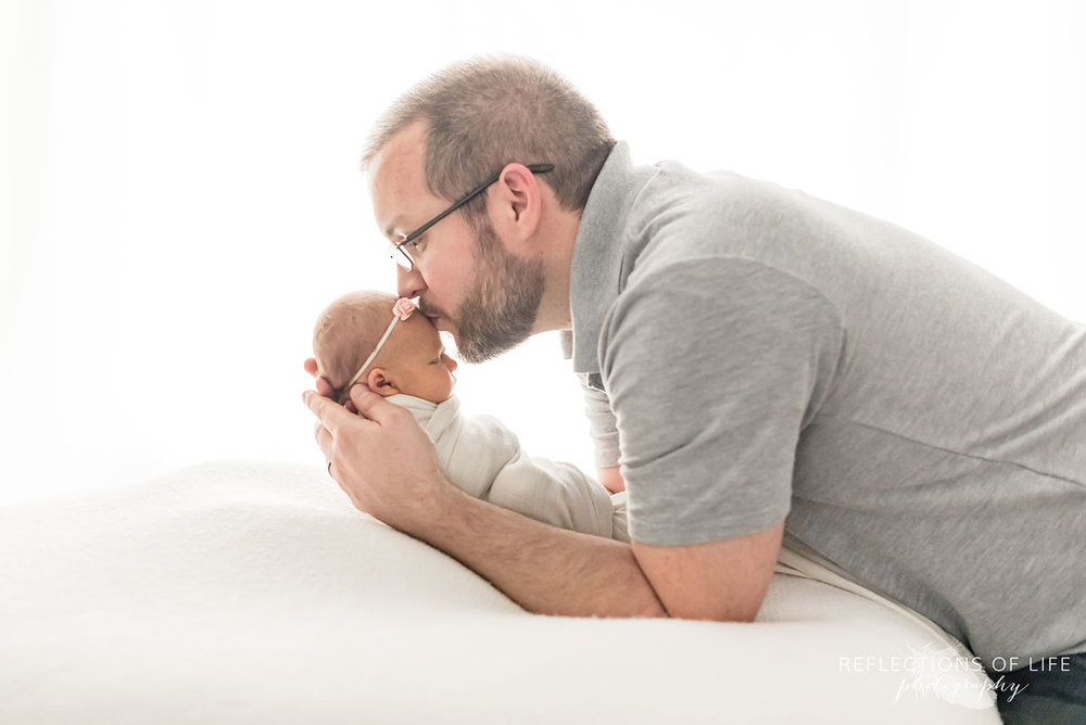 New dad kissing baby girl on white beanbag in natural light