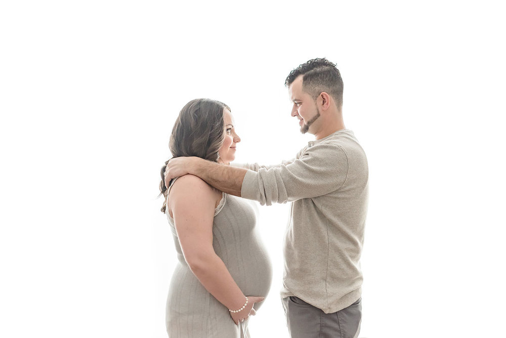 Niagara Ontario maternity photo studio dad putting his arms around expecting mom