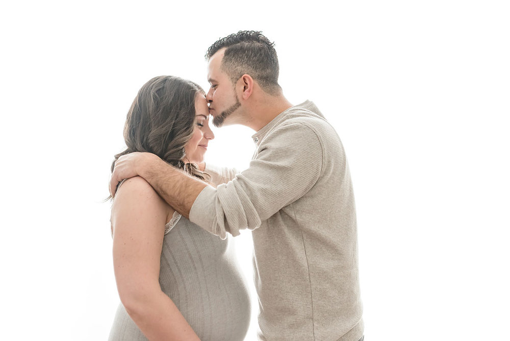 Dad kisses expecting mom on the forehead