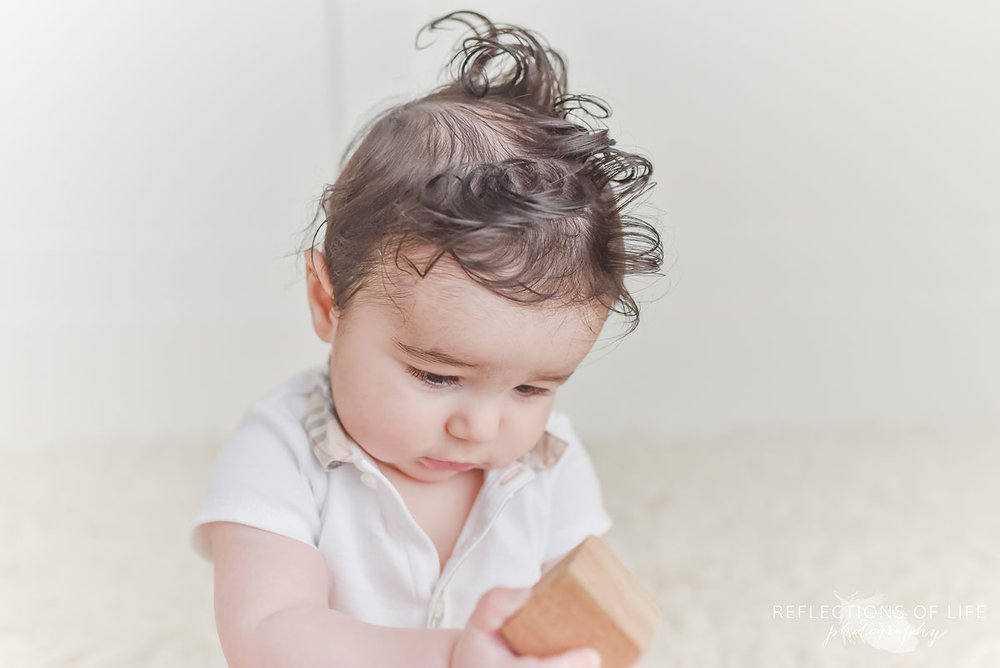 baby boy playing with wood blocks in a white studio in grimsby ontario Canada
