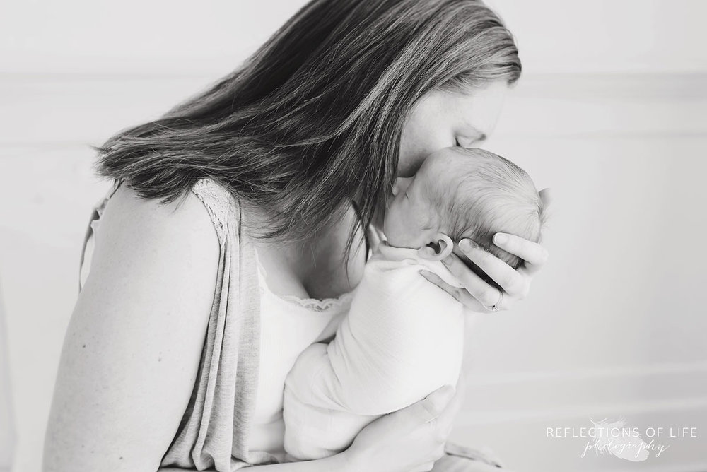 black and white image of mom whispering into baby's ear
