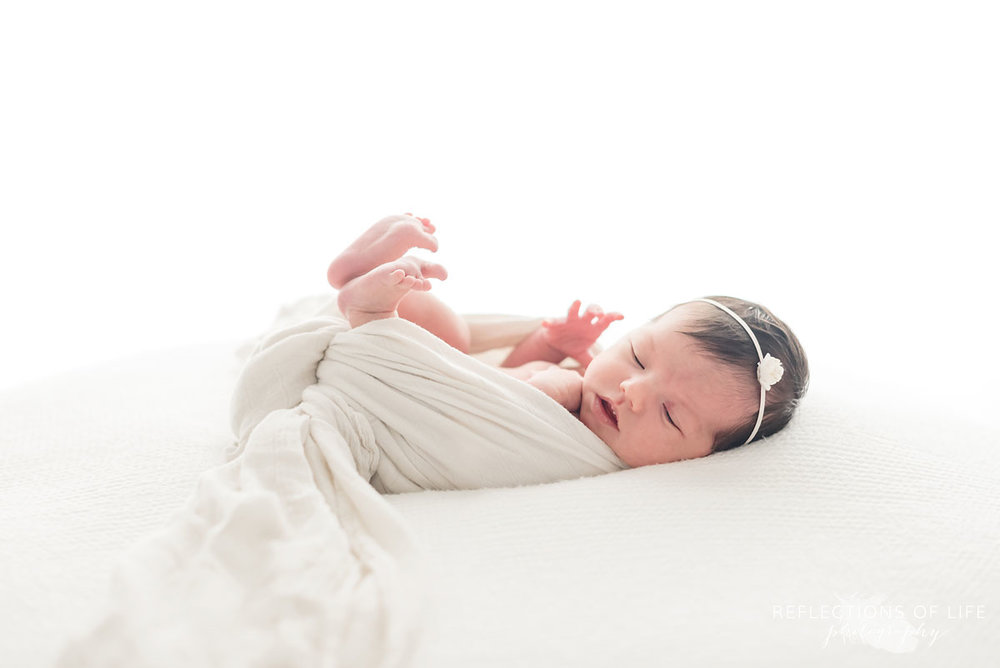 newborn photography of baby wrapped in white