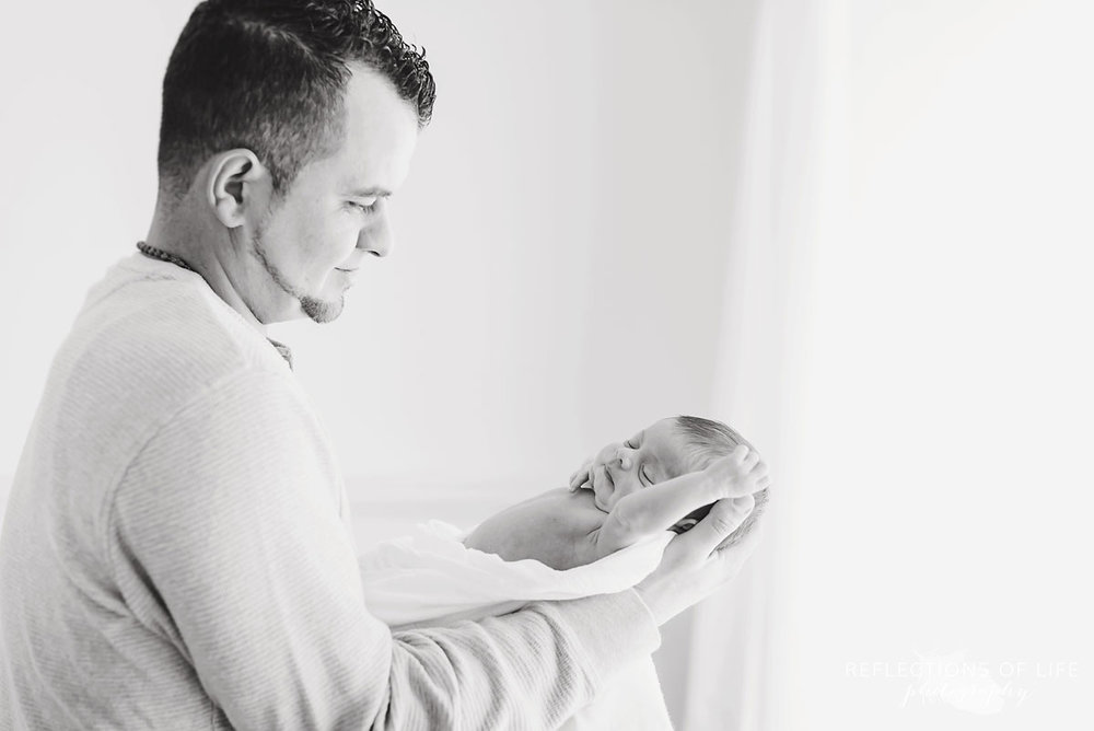 Newborn in her daddy's arms in Grimsby Ontario white studio