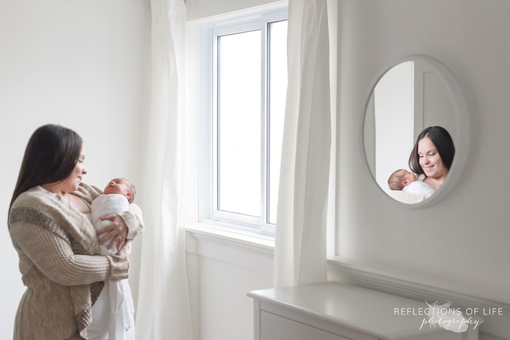 mom and newborn daughter in natural light studio with mirror reflection.jpg