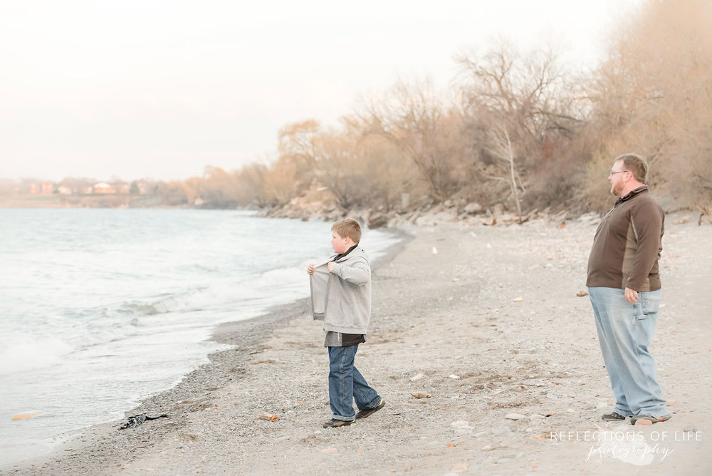Father and son throwing rocks into the water by Grimsby Beach