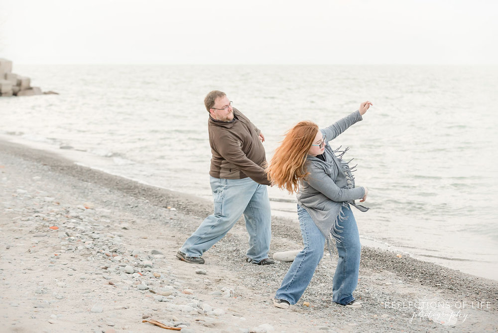 Father and daughter throwing stones into the water Grimsby Ontario