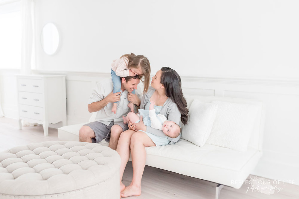 Candid family photoshoot on a couch in white studio