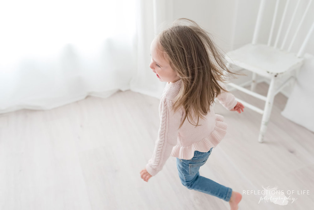 Little girl running around in white studio