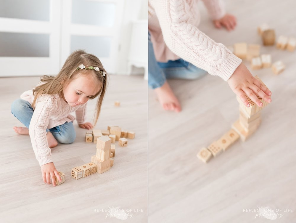 Young girl with flower headband on building with blocks in white studio