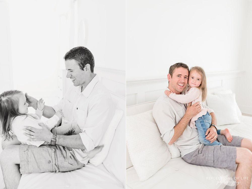 Father and daughter playing around on white couch