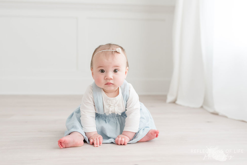 Baby looking at camera on floor in white studio