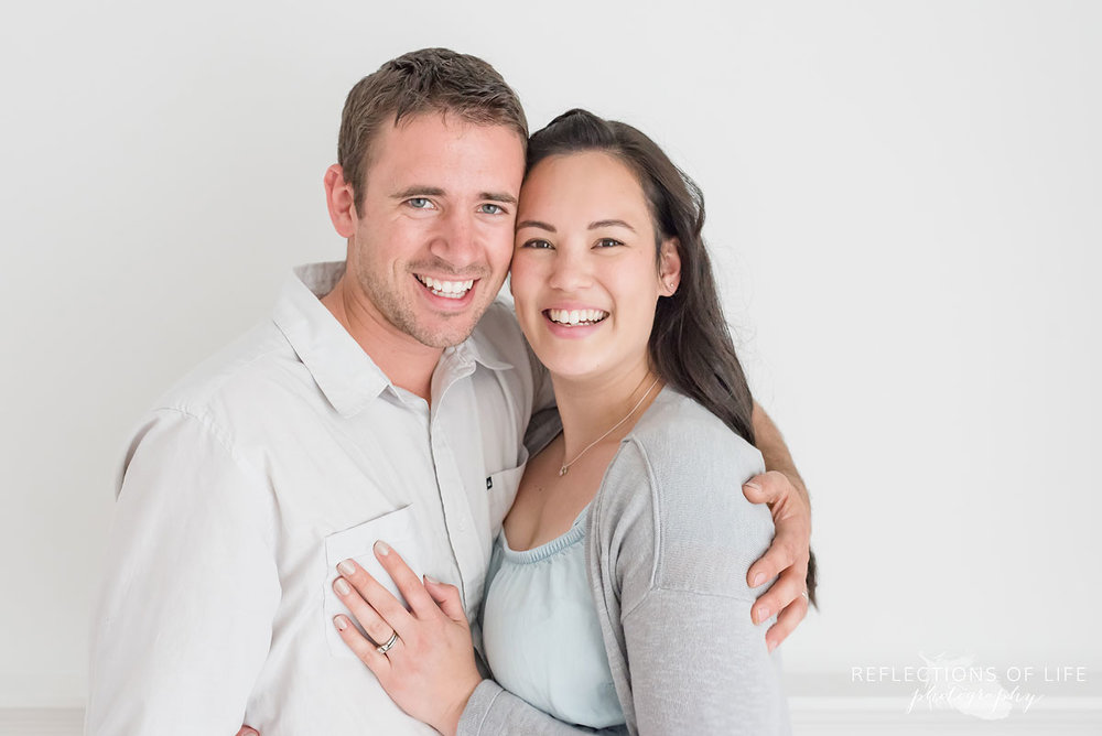 Husband and wife smiling in white studio