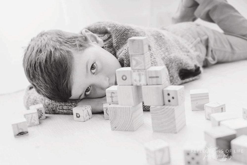 little boy relaxing while playing with wooden blocks