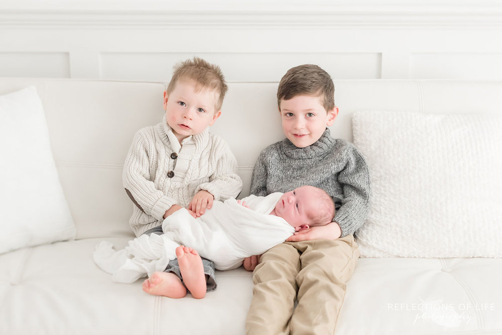 Siblnigs holding their newborn baby brother in white studio