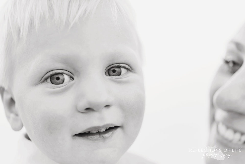 Black and white photo of little boy looking into the camera lens