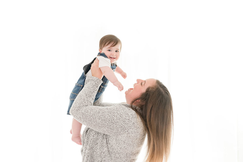 Mother swinging baby around in white studio