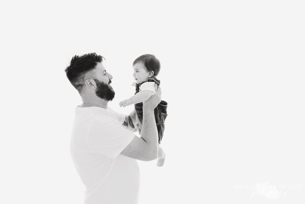 Father smiling baby white holding him up in black and white