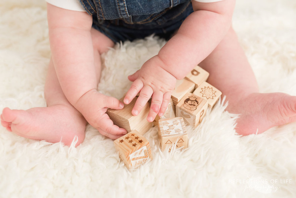 Baby playing with wooden blocks on white blanket