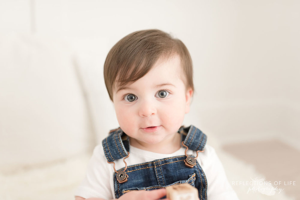 Baby looking at camera on white couch