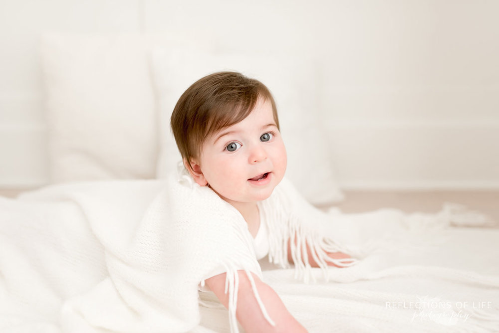 Baby looking at camera and smiling in white blankets