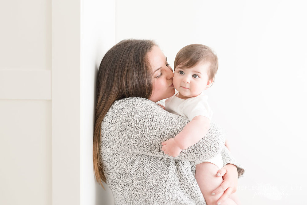 Mother kissing baby on cheek white holding baby up