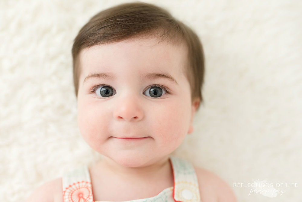 Baby smiling at camera on white blanket