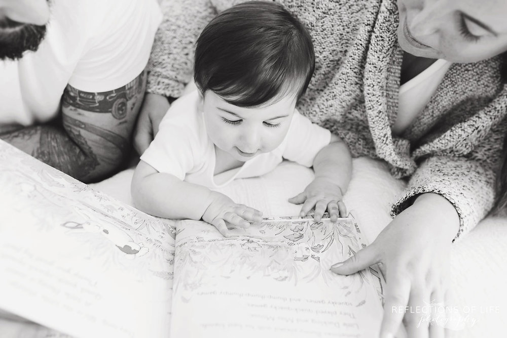 Baby looking at pictures in a book black and white