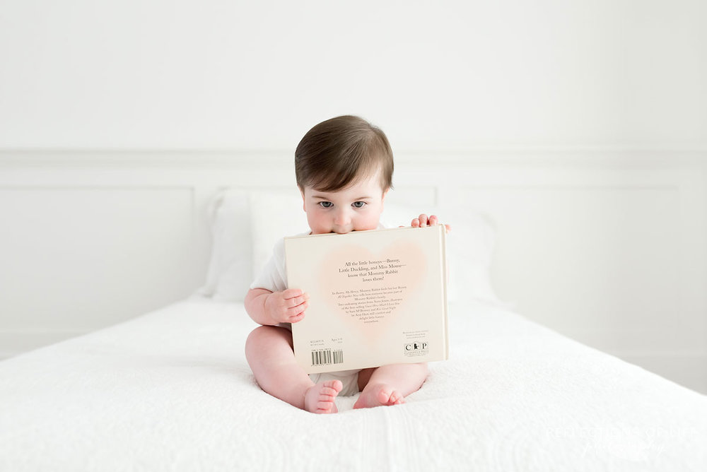 Baby putting edge of a book in mouth on white couch