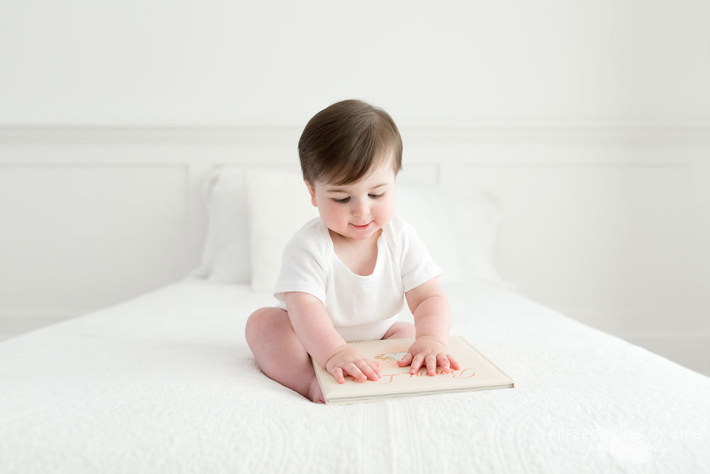 Baby looking at cover of book on white couch Grimsby Ontario