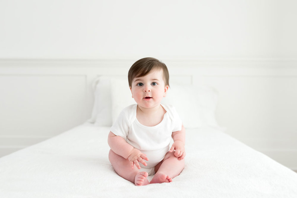Baby with open mouth on white couch in Niagara