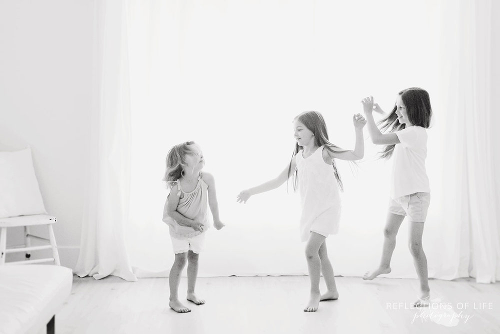 three sisters dancing in white studio