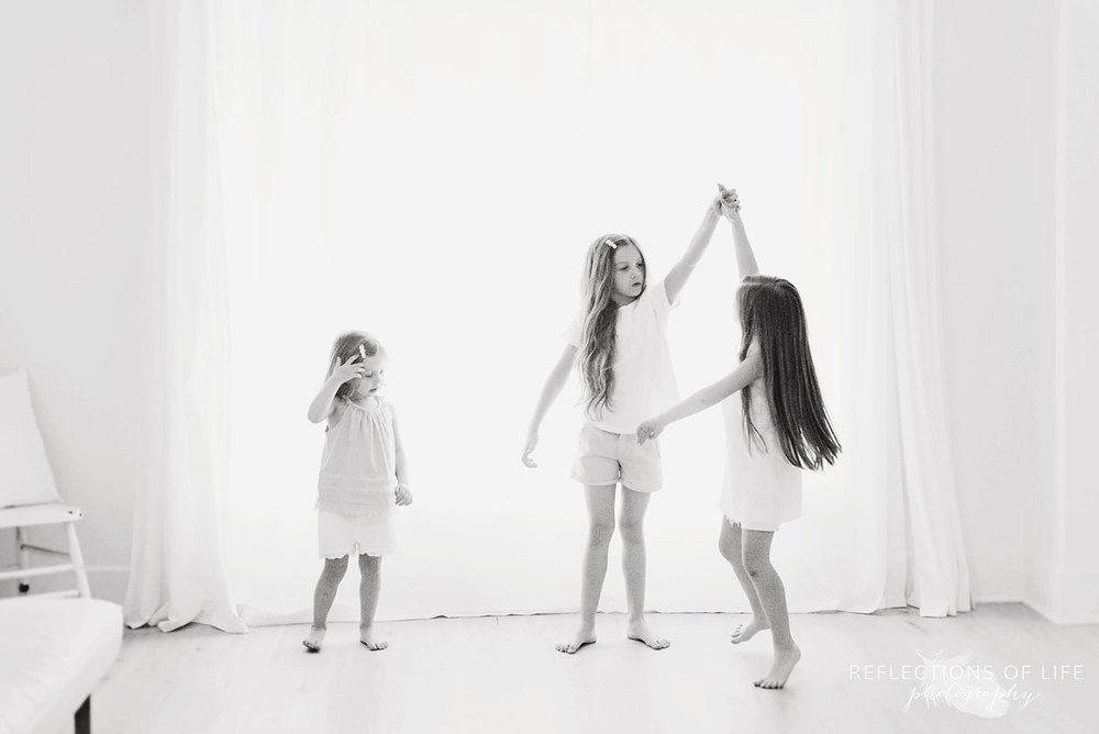 portrait of three sisters spinning each other in front of white background