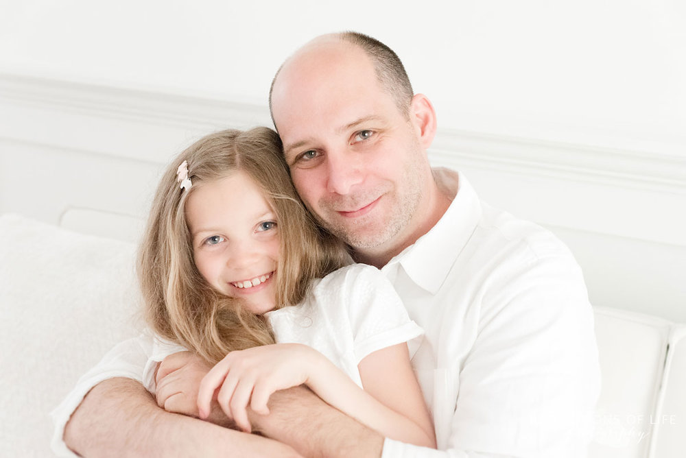 dad and daughter sitting on white couch
