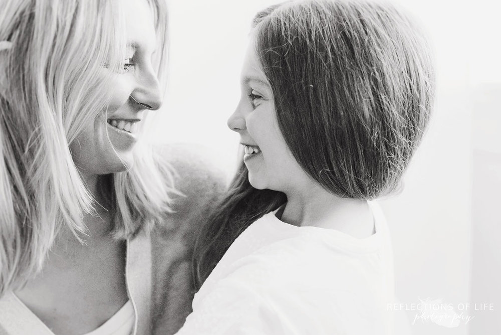 mother and daughter looking at each other white background