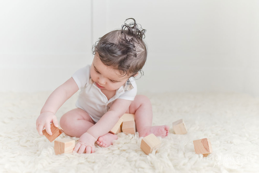 baby+boy+playing+with+wood+blocks+in+white+studio.jpg