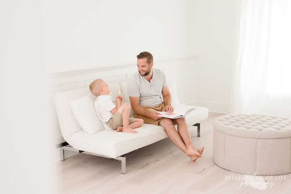 father and son laughing togeher in studio on white couch