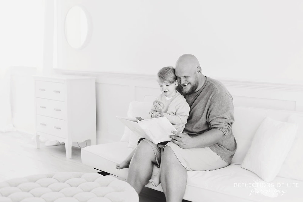 father reading to son on white couch in studio black and white
