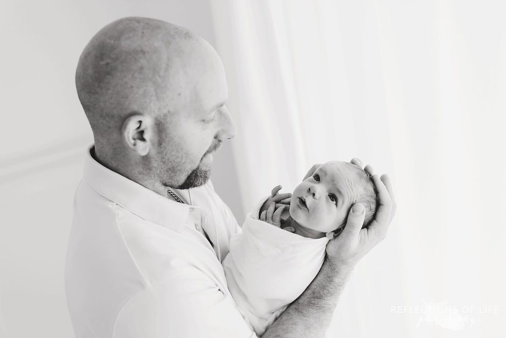 dad holding son in studio black and white
