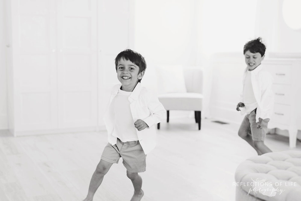 black and white young boys in studio chasing each other
