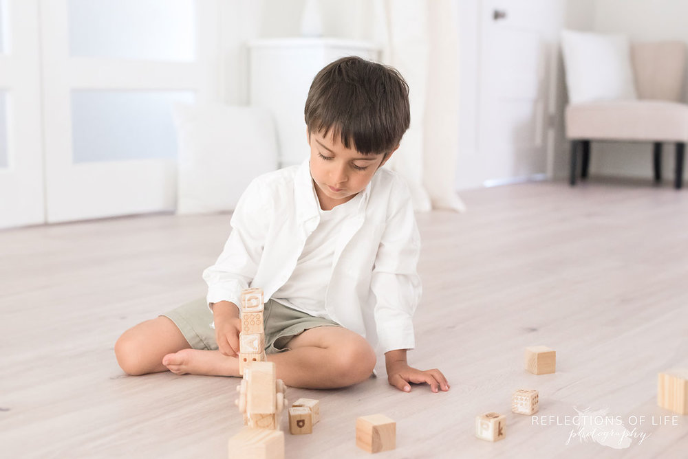 boy playing with blocks on studio floor