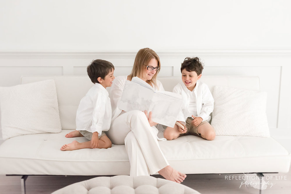 family reading in studio white background