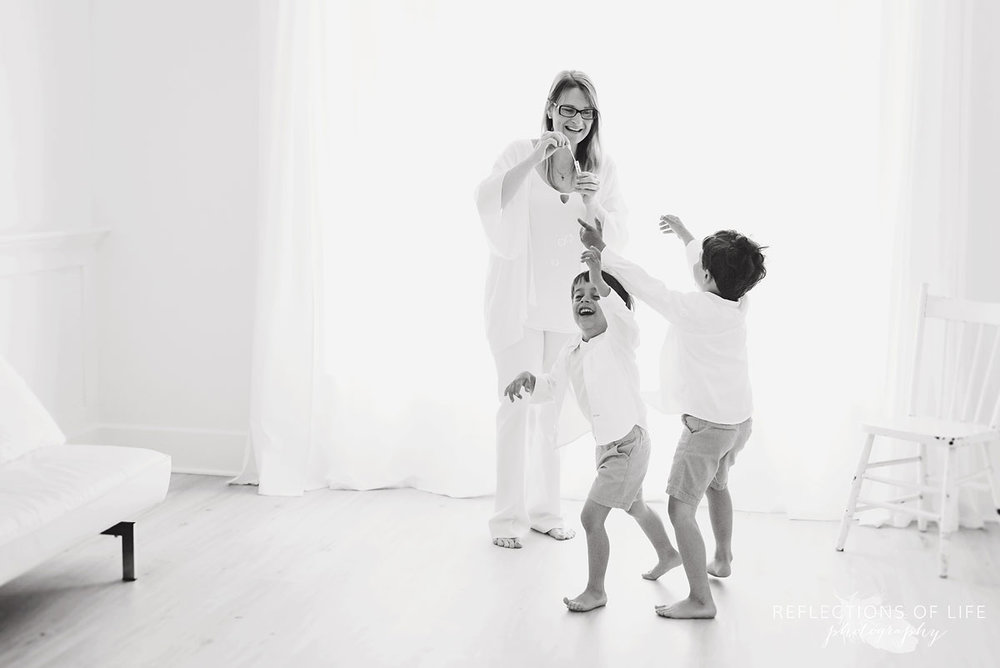 mother dancing with two boys in studio black and white