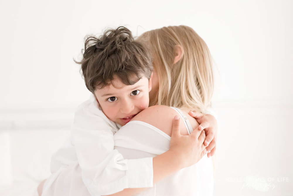 portrait of young boy hugging his mom in studio